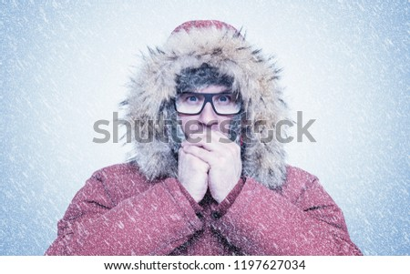 Frozen man in red winter clothes and glasses warming hands, cold, snow, frost, blizzard #1197627034