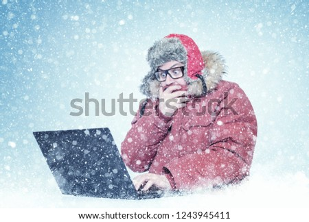Frozen man in red winter clothes and glasses working on a laptop in the snow. Cold, frost, blizzard, computer