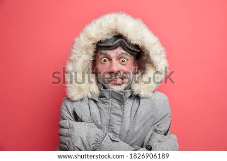 Frozen man trembles from cold has red face covered by ice frosted beard wears jacket with hood needs to warm during winter expedition poses over coral background. Cold weather low temperature Stockfoto ©