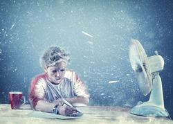 Frozen man working at office beside a powerful fan , fan causing snow