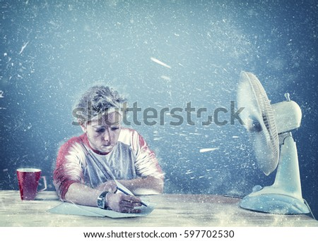 Frozen man working at office beside a powerful fan , fan causing snow