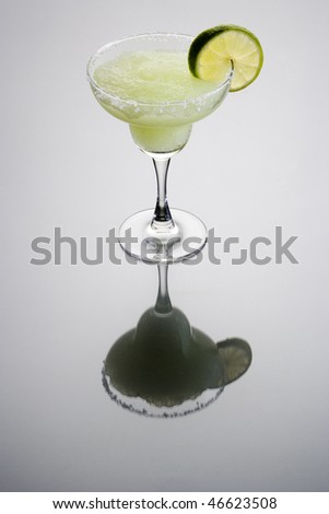 Frozen Margarita mixed drink with lime slice garnish on plain grey background with reflection