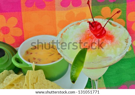 Frozen margarita with maraschino cherry and lime on brightly colored background served with chili con queso dip and tortilla chips.