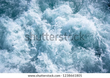 Frozen motion of churning blue water on a sea with lots of abstract turbulence and white splash on the surface