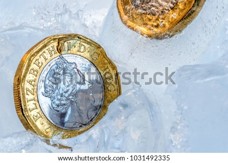 Frozen New British one pound sterling coin up close macro inside ice cubes #1031492335