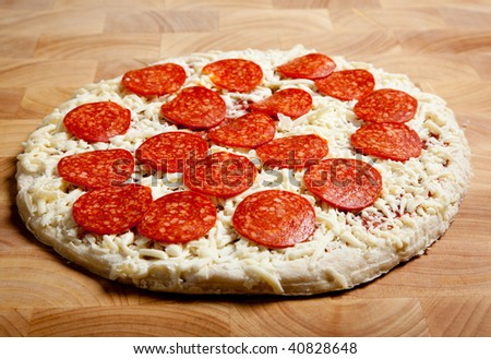 Frozen pepperoni and Cheese pizza on a wooden cutting board
