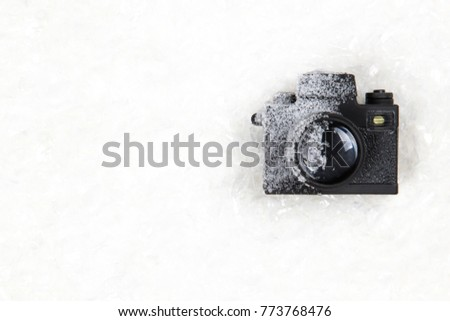 Frozen photo camera on the white snow background with copy space. Winter photography / photo shooting