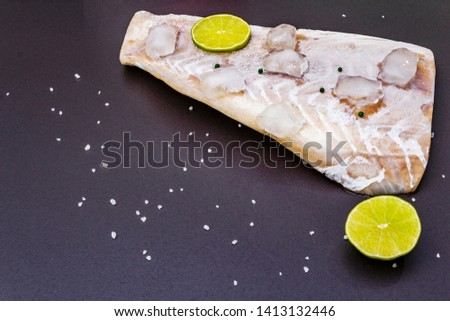 Frozen pollock fillet with pieces of ice. Concept of healthy seafood. Organic fish on a black stone background, copy space, copy space