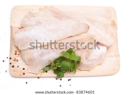frozen pollock (pallock) and spices on wooden board isolated