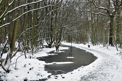 Frozen pond or pool, path with wooden bench and snow covered trees. Outdoors on a freezing cold winters day in ancient Norsey woodland forest. Billericay, Essex, United Kingdom, February 9, 2021