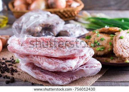 Frozen pork neck chops meat and pork schnitzel in a plate #756012430
