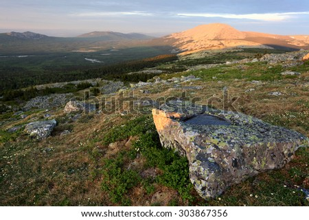 Frozen puddle in stone on the backdrop of Iremel mountain is lit by rising sun in late spring, South Urals, Russia.