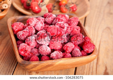 frozen raspberries in the wooden bowl