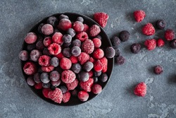 Frozen raspberry, blueberry, cranberry on black background. Frozen fruit. Top view, flat lay, close up.