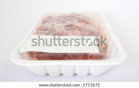 Frozen raw supermarket meat on white, isolated, copy space, close-up, macro.
