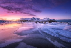 Frozen sea coast at colorful sunset in Lofoten islands, Norway. Snowy mountains, sea with frosty shore, ice, reflection in water, purple sky . Winter landscape with snow covered rocks, fjord at night