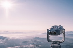 Frozen, snow covered touristic Coin Operated Binocular viewer over mountain skyline winter landscape