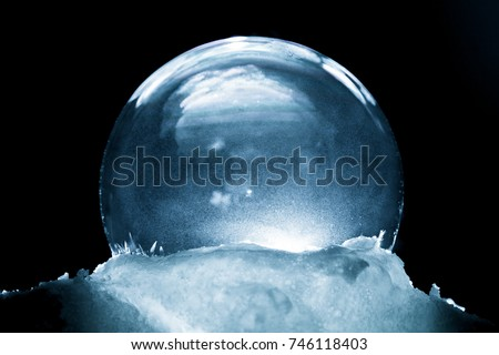 Frozen snow globe christmas magic ball with flying snowflakes. Winter Background. Christmas and New Year Holidays precious backdrop. Ice patterns frosted on ball of soap against dark black abstract #746118403