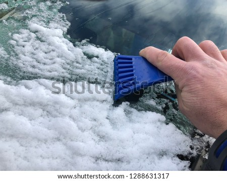 frozen snow on autocar in wintertime. Sky is reflected on the windshield of the car.