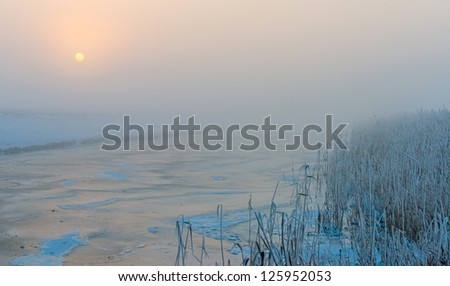 Frozen snowy canal in winter at dawn - stock photo