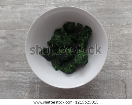 Frozen spinach portions defrosting in a bowl