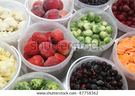 Frozen summer fruits and healthy vegetables in plastic containers - stock photo