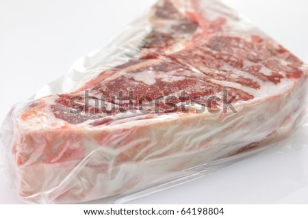 frozen t-bone steak wrapped in plastic