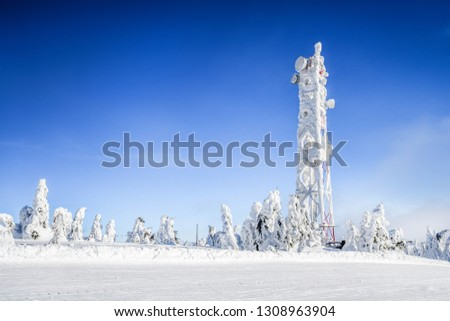 Frozen television or cellular tower in heavy snow near ski center. Telecommunication towers with dish and mobile antenna against blue sky in winter mountains. #1308963904