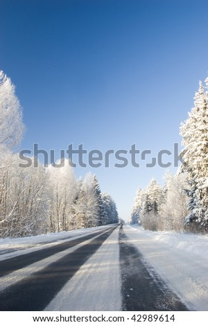 Frozen trees and snowy land road at winter, deep blue sky