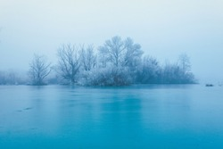 Frozen turquoise lake in misty winter morning, with trees without leaves on a small island across the lake