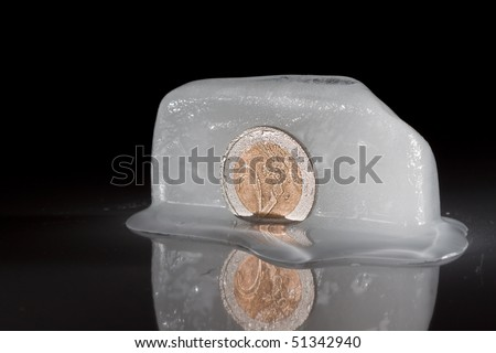 Frozen two euro coin on black isolated background - stock photo