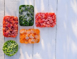Frozen vegetables in geometric shapes on a wooden table. top view. harvesting and preserving vitamin veggies for winter. frozen carrots, green peas, onion and bell pepper. healthy food storage.