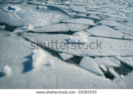 Frozen water surface with cracked ice - stock photo