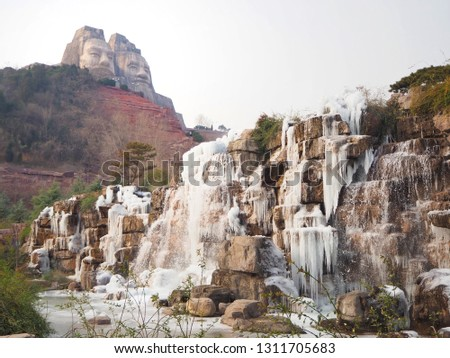 Frozen waterfall and The sculpture of Emperors Yan and Huang in Zhengzhou, Henan province, China.