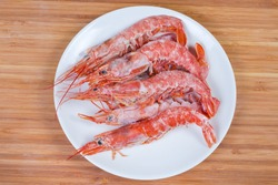 Frozen wild Argentinian red shrimps with heads on dish on a wooden surface, top view