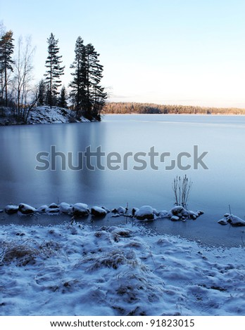 Frozen wilderness lake scenery, blue ice reflection