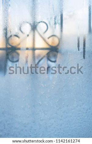 Frozen window with carved lattice slightly thawed from morning sun.