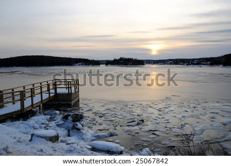 Frozen Winter Dock and Ocean at Sunset