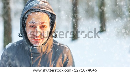 Frozen young man in a jacket with a hood covered with snow in winter forest. Snowflakes lie on the eyelashes, eyebrows, cheeks.