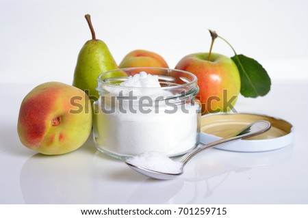 Fructose, or fruit sugar in glass jar. With fruit