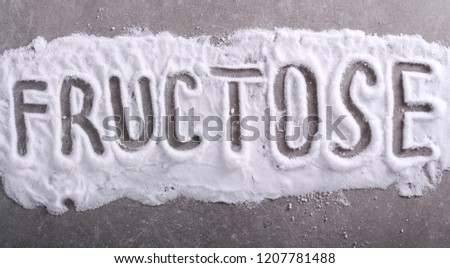 Fructose word written in fructose powder over grey background