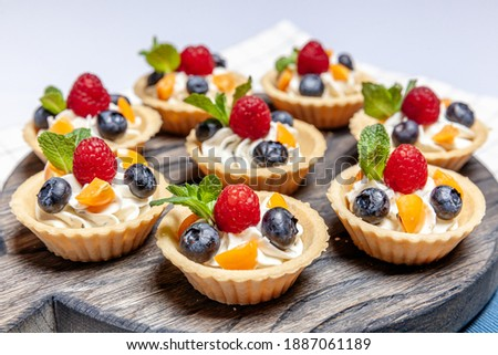 Fruit and berry tartlets dessert assorted on wooden tray. Closeup of delicious pastry sweets pies colorful cakes with fresh natural raspberry blueberry and cheese cream. French bakery catering