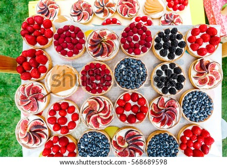 Fruit and berry tartlets dessert tray assorted top view background. Beautiful delicious tarts, pastry cakes sweets with fresh raspberries, figs, strawberry. French Bakery catering outdoors. Filtered