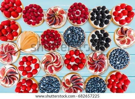 Fruit and berry tartlets dessert tray top view on blue wood background. Beautiful delicious tarts, pastry cakes sweets with fresh raspberries, figs, strawberry. French Bakery
