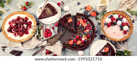 Fruit and berry tarts dessert on grey backgrond. Summer dessert concept.   Perfect for party. Top view, copy space, panorama, banner