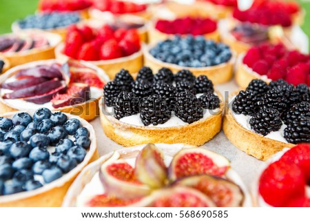 Fruit and berry tarts dessert tray assorted. Closeup of beautiful delicious pastry sweets with fresh natural blackberries and figs. French Bakery catering. Filtered, shallow depth of field