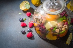 Fruit and berry tea in teapot. Hot drink with lemon, mint, blueberry, ginger, orange, apple. Hot flavored steam beverage on dark blue background copy space