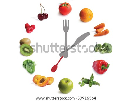 fruit and vegetable clock with knife, fork and spoon on a white background