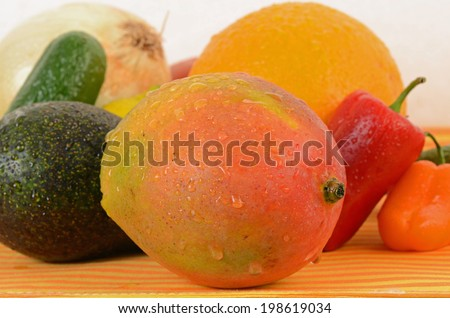 Fruit and vegetable Ingredients for making Spicy Mango Salsa spread over orange and yellow striped base with neutral background.