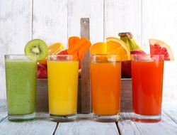 Fruit and vegetable juice in glasses and fresh fruits in box on wooden table on wooden wall background